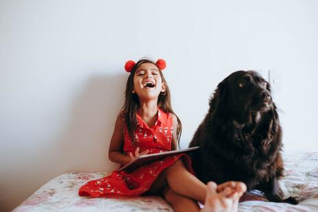 girl laughing with her dog